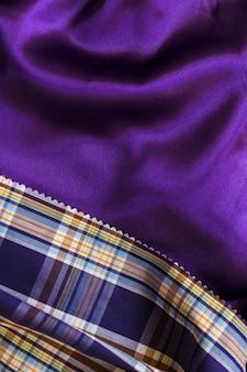 Тартанский текстильный узор на гладкой фиолетовой ткани