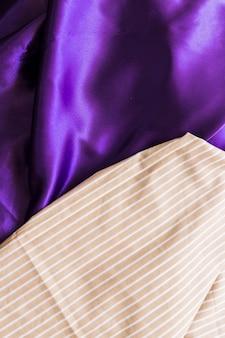 Повышенный вид текстильной ткани с прямыми линиями на шелковистой фиолетовой драпе