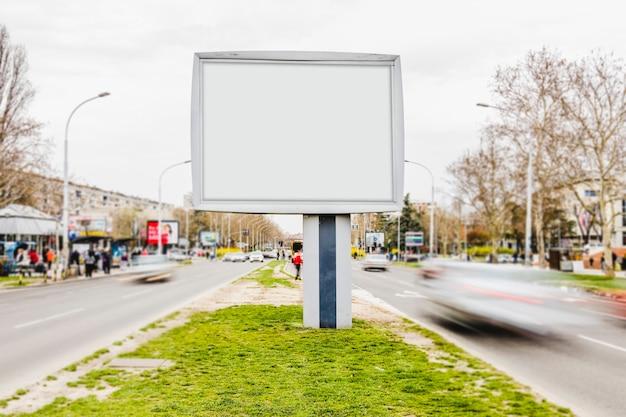 忙しい通りの白い広告掲示板の模擬