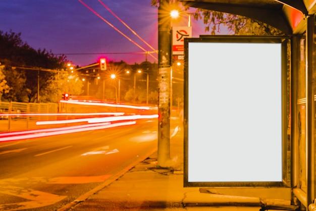夜のバス停留所にブランクのビルボード