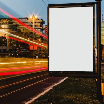夜に街のライト・トレイルを持つ空白の白い看板