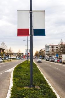 ダブルサイドの空白の広告の旗、通りのランプのポールにハングアップ