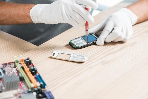 携帯電話を修復する技術者の手のクローズアップ