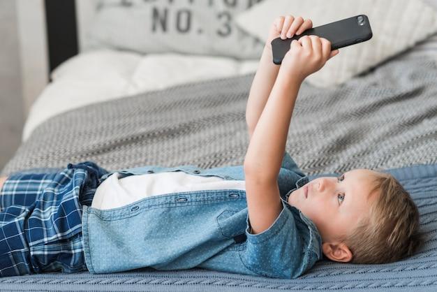 携帯電話を使ってベッドに横たわっているブロンドの少年