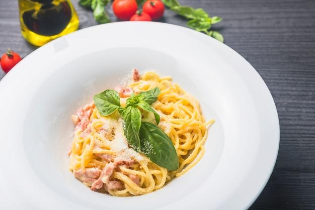 白いプレートにチーズとベールの葉を入れたスパゲッティのガーニッシュ