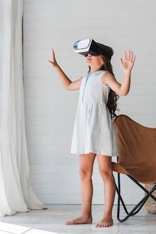 仮想現実のゴーグルを着ている幸せな少女