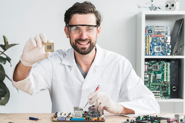 Портрет счастливый молодой мужчина техник, держащий компьютерный чип