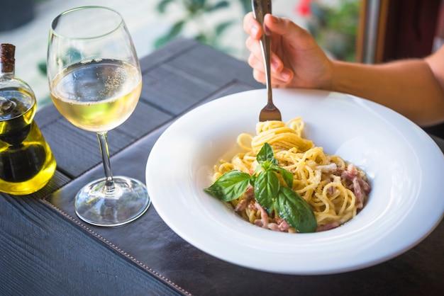 テーブル、ワイングラス、スパゲッティを食べる人のクローズアップ