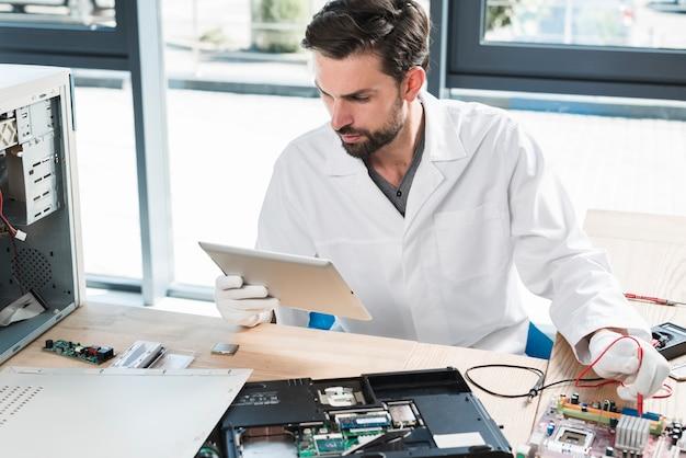 ワークショップでコンピュータを修復しながらデジタルタブレットを見ている男