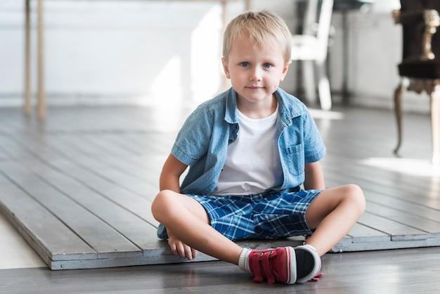 家の木の床に座っている可愛い少年の肖像