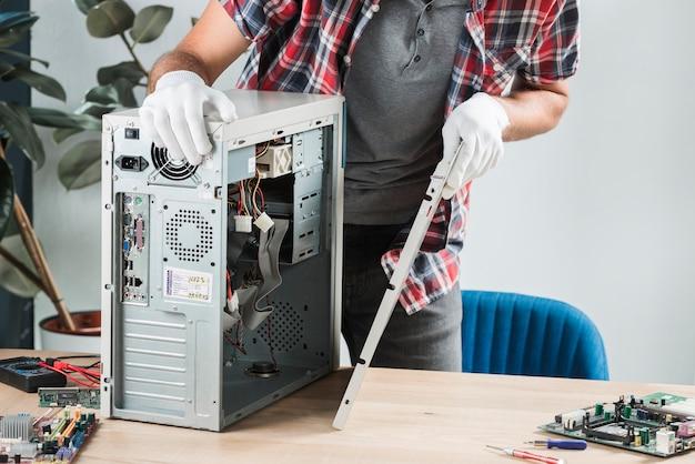木製の机の上にコンピュータを組み立てている男性技術者の中央部の図