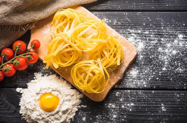 Сырой тальятелле на разделочной доске с яичным горшком в муке и помидорах на деревянной доске
