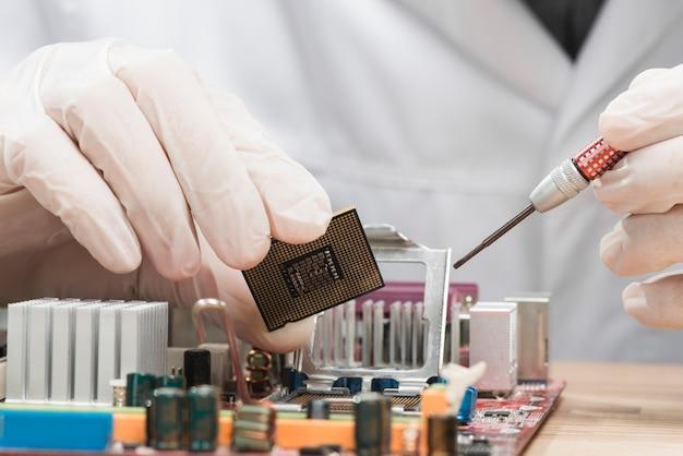 男性の技術者の手は、コンピュータチップを保持