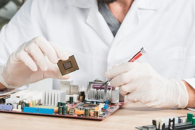 Крупный план мужского техника, держащего компьютерный чип