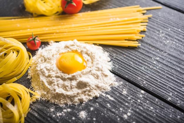 Тальятелле и спагетти с яичным желтком на муке над деревянным столом