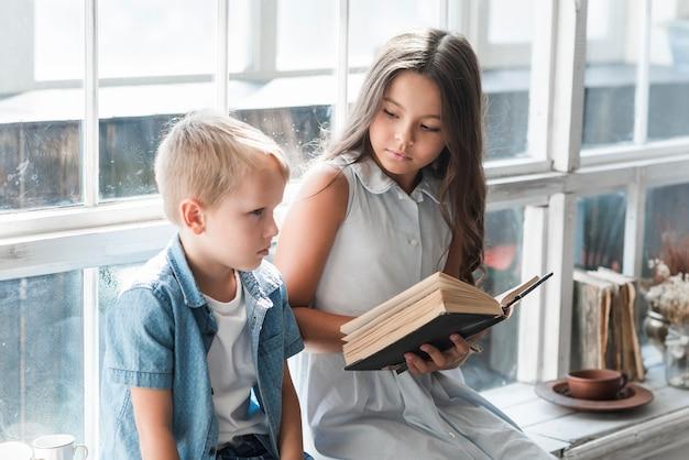 窓の敷居の読書の近くに座っている少年のクローズアップ