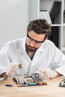 木製の机の上にマザーボードを持つコンピュータチップを保持している技術者