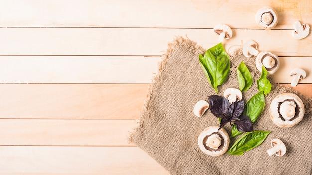 木製の厚板の上にジュート袋に葉の野菜を入れたキノコ