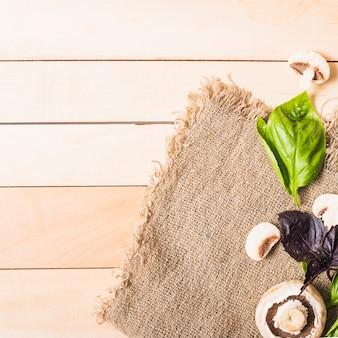 木製の厚板の上にジュート袋のバジル葉とキノコ