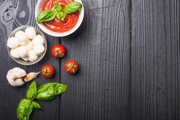 トマトソースとモッツァレラのボウルとバジルとガーリックの木製テーブル
