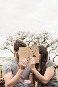 彼らの顔を本で覆うカップルのクローズアップ