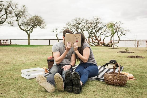 ピクニックで彼らの顔の上に本を持っている毛布に座っているカップル