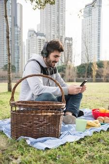 ピクニック、携帯電話を使用してヘッドフォンで音楽を聴く男のクローズアップ