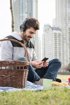 公園に座っている若い男を笑って、携帯電話で音楽を聴いている