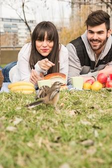 緑の草の上に雀を探してピクニックで若いカップルに笑顔