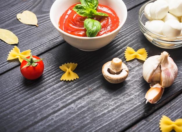 トマトソースのボウルとバジル