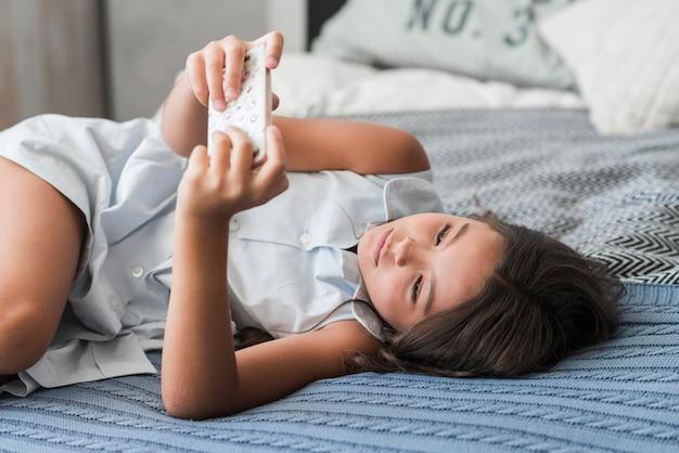 スマートフォンを使ってベッドに横たわっている少女