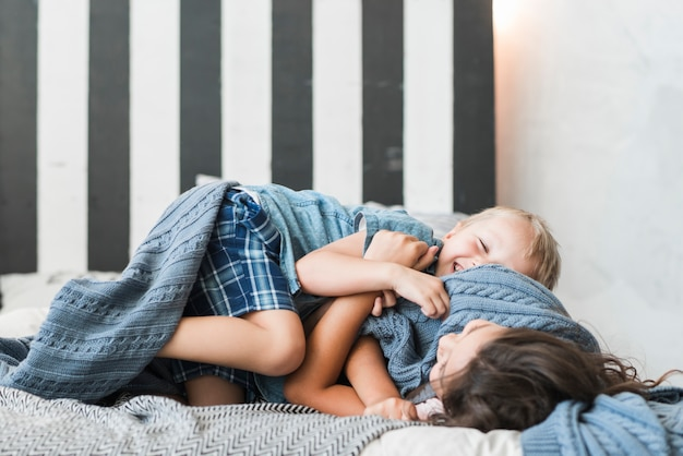 幸せな男の子と女の子がベッドで遊ぶ