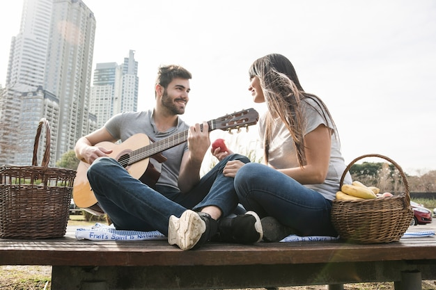 ピクニックでギターを弾く男を見る笑顔の女性