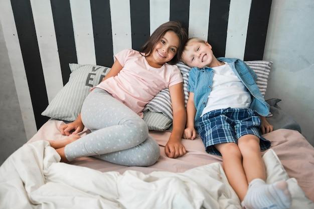 家庭のベッドに横たわっている笑顔の少女と少年