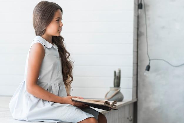 Вид сбоку красивая девушка чтение книги