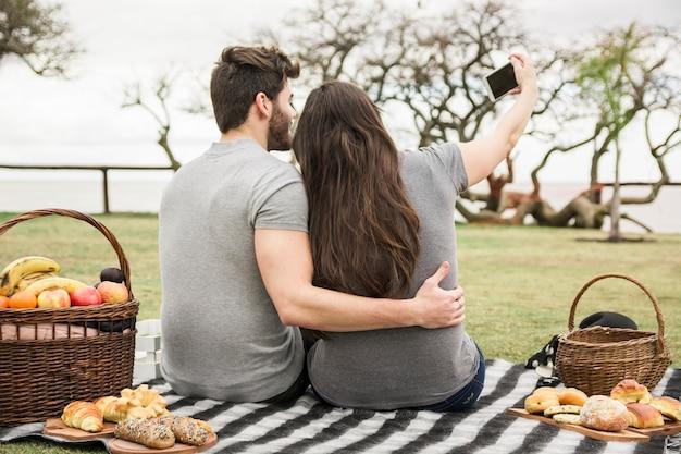 Вид сзади молодой пары, принимая автопортрет на мобильный телефон в парке