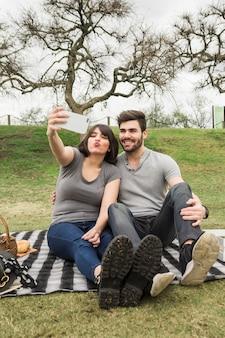 携帯電話でセルフを取ってピクニックに幸せな若いカップルの肖像