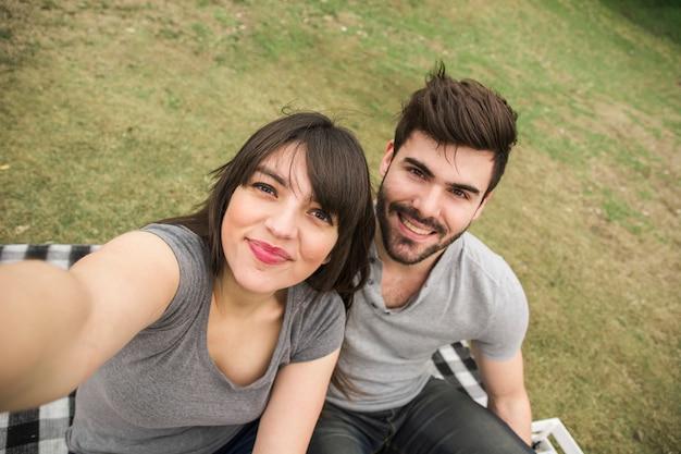 幸せな若いカップルは、公園でセルフを取って