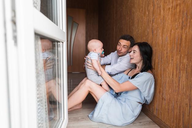 赤ちゃんと遊んでいる窓の近くの床に座っている若いカップル