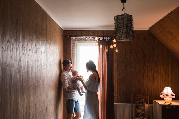 自宅で赤ちゃんと遊んでいる窓の近くに立っているカップル