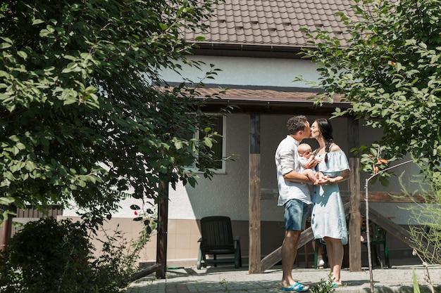 自宅の前でキスをしている赤ちゃんを運ぶカップル