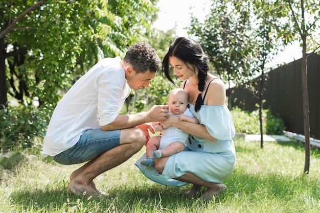 庭で赤ちゃんを愛する両親