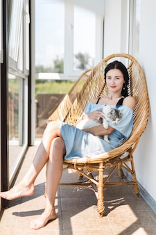 パティオで木製の椅子に猫と座っている若い女性