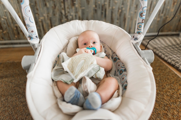 かわいい赤ちゃんのおしゃぶりは、自宅で乳母車に横たわっ