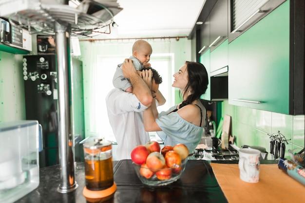 キッチンに立っている男の肩に座っている赤ちゃんと遊んでいる母親