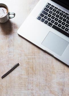 木製の背景にコーヒーカップとペンが付いている開いたラップトップ