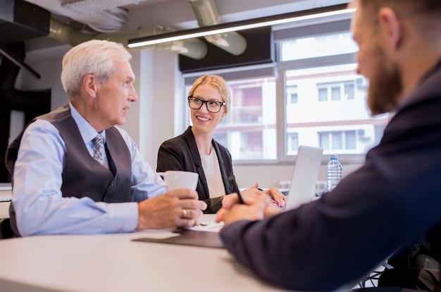 オフィスで彼の同僚と座ってコーヒーカップを保持する上級のビジネスマン