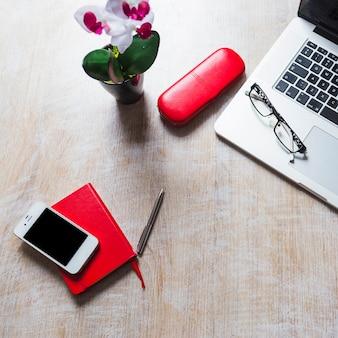 ノートパソコンの上の文房具と携帯電話の机上のオーバーヘッドビュー