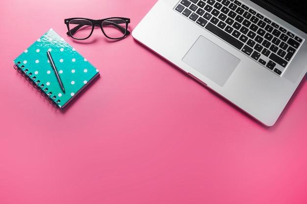 スパイラルノートのペン;ピンクの背景に眼鏡やラップトップ
