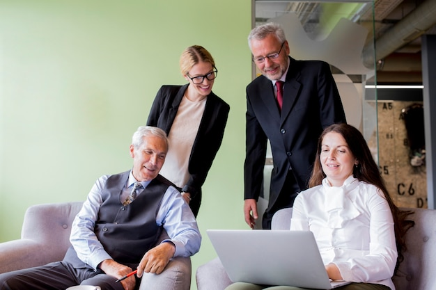 オフィスで彼女の同僚にラップトップを表示して自信を持っているビジネスマンを笑顔